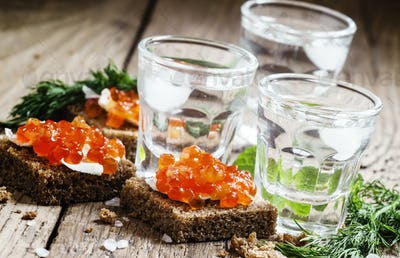 Cold Russian vodka with ice and small snacks sandwiches with butter and red salmon caviar