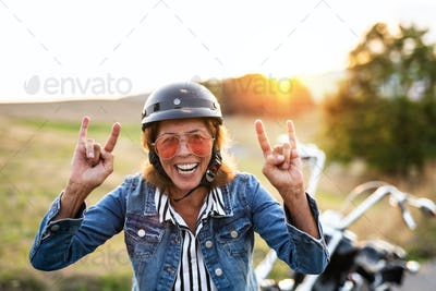 A cheerful senior woman traveller with motorbike in countryside at sunset.