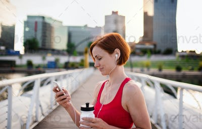 Young woman with smartphone resting after doing exercise on bridge outdoors in city.
