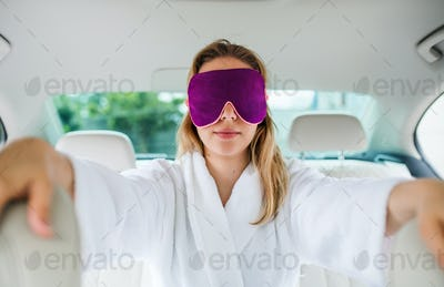 Young woman with dressing gown and eye mas sitting in car, resting.