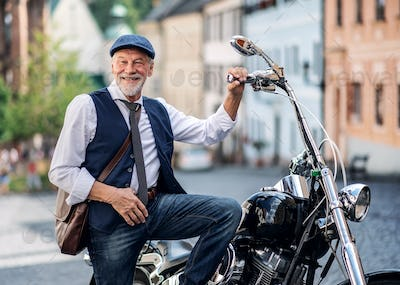 A senior businessman with motorbike in town.