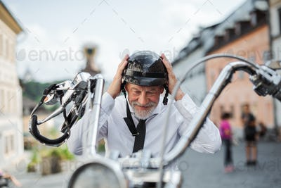 A senior businessman with motorbike in town, putting on helmet.