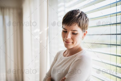 Portrait of young woman standing by window indoors at home, daydreaming.