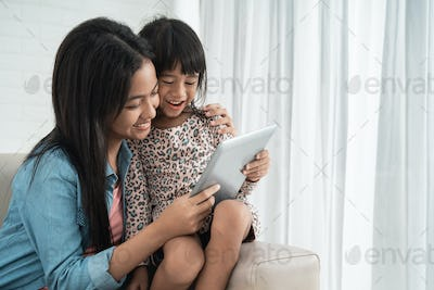 sibling sister sitting on a couch and using tablet