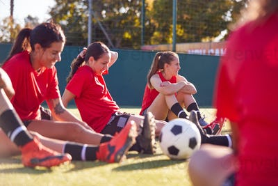 Womens Football Team Stretching Whilst Training For Soccer Match On Outdoor Astro Turf Pitch