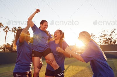 Womens Football Team Celebrating Winning Soccer Match Lifting Player Onto Shoulders