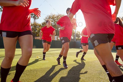 Womens Football Team Run Whilst Training For Soccer Match On Outdoor Astro Turf Pitch