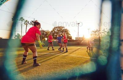 View Through Goal Net Of Womens Football Team Playing Soccer Match