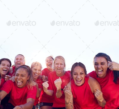 Portrait Of Womens Football Team Celebrating Winning Soccer Match On Outdoor Astro Turf Pitch