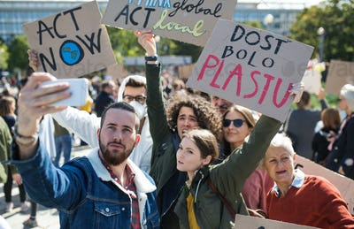 People with placards and posters on global strike for climate change, taking selfie.