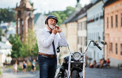 A senior businessman with motorbike in town, putting on helmet
