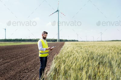 An engineer standing on a field on wind farm, making notes