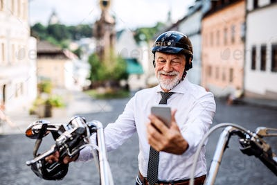A senior businessman with motorbike in town, using smartphone