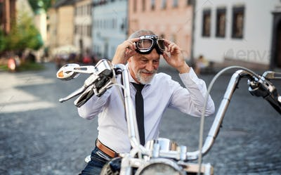 A senior businessman with motorbike in town, putting on goggles