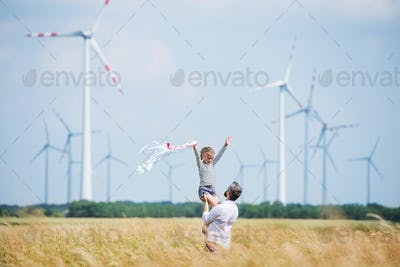 Mature father with small daughter standing on field on wind farm