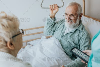 Senior patient gets up from the hospital bed by helping himself with a special handle