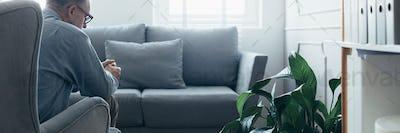 Senior counselor sitting in grey wing back chair in elegant Scandinavian interior