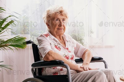 Elderly ailing woman dressed in a blouse with flower pattern is sitting in a wheelchair in her home