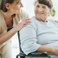 Happy caregiver with elder patient on the wheelchair