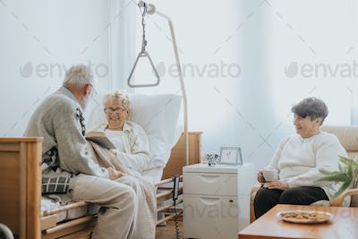 Senior people visiting injured friend in the hospital