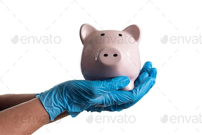 Doctor or Nurse Wearing Surgical Gloves Holding Piggy Bank Isolated on White