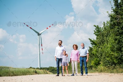 Multigeneration family walking on field on wind farm