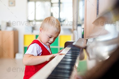 A down-syndrome school boy sitting at school, playing piano
