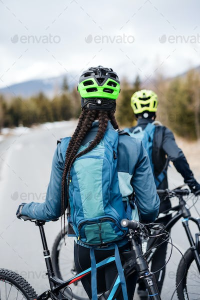 Rear view of two mountain bikers on road outdoors in winter