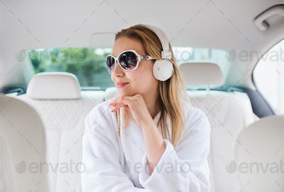 Young woman with sunglasses and headphones sitting in car in dressing gown