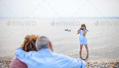Small girl with camera and grandparents on holiday ba lake, taking photos