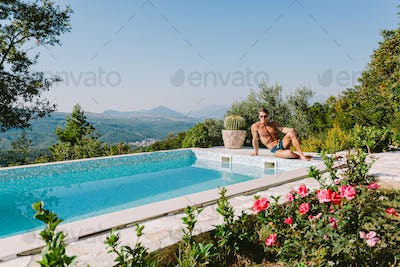 Handsome muscular man relaxing in swimming pool outdoors on summer day
