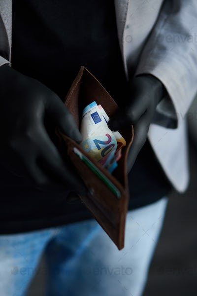 Man holding a wallet with money euro in hand in black medical gloves.