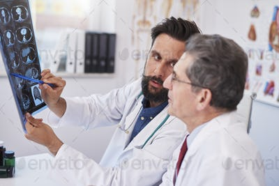 Two busy doctors discussing x-ray image