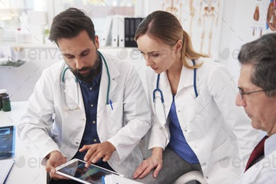 Three doctor working with tablet in doctor's office