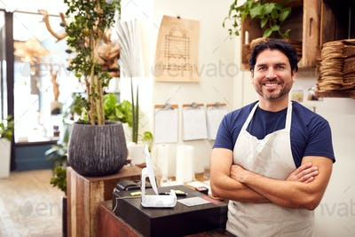 Portrait Of Smiling Male Sales Assistant Standing By Sales Desk Of Florists Store
