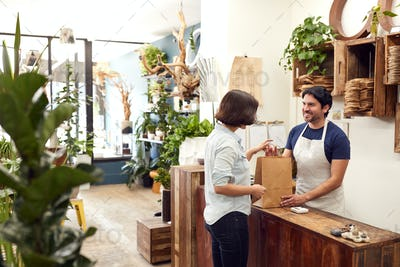 Male Sales Assistant In Florists Shop Serving Female Customer At Sales Desk