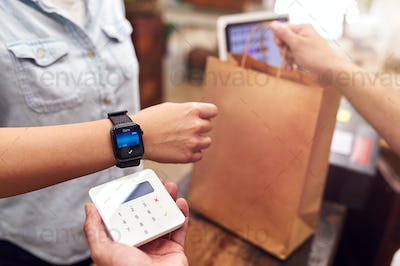 Close Up Of Woman In Store Making Contactless Payment At Sales Desk Holding Smart Watch To Reader