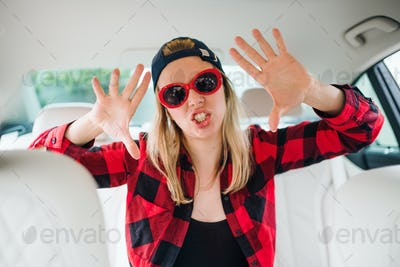 Young woman with sunglasses sitting in car, having fun