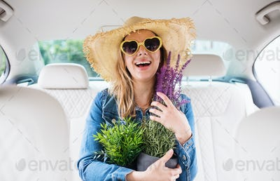 Young woman with hat and sunglasses sitting in car, holding plants