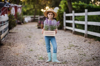 A front view of small girl standing outdoors on family farm, holding plants