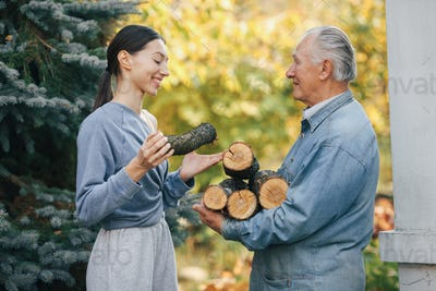 Grandfather with granddaughter on a yard with firewood in hands