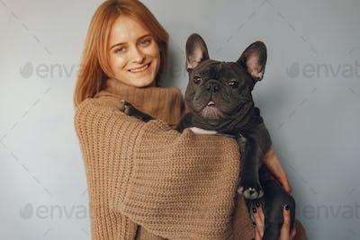 Elegant woman in a brown sweater with black bulldog