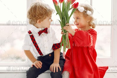 Elegant little kids in a studio with bouquet of tulip