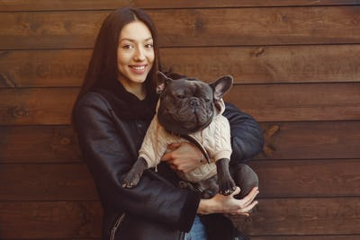 Elegant woman in a black jacket with black bulldog