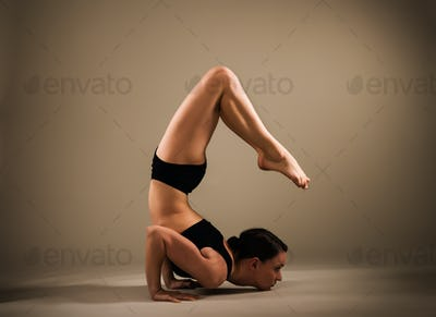 Slim athletic young woman doing a handstand