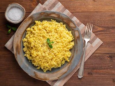 Bulgur wheat. Boiled bulghur cereal in plate on brown wooden table. Healthy vegetarian
