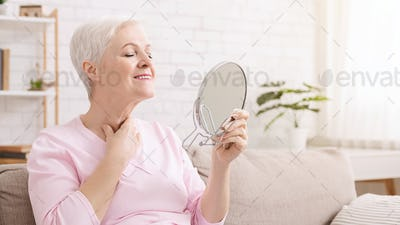 Senior lady looking at mirror, sitting on quarantine at home