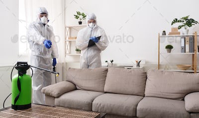 Men in virus protective suit making treatment of sofas