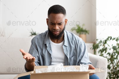 Purchase delivery error. Surprised man opened package