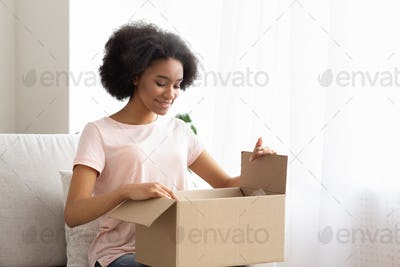 Satisfied young woman customer sit on sofa, unpack package parcel